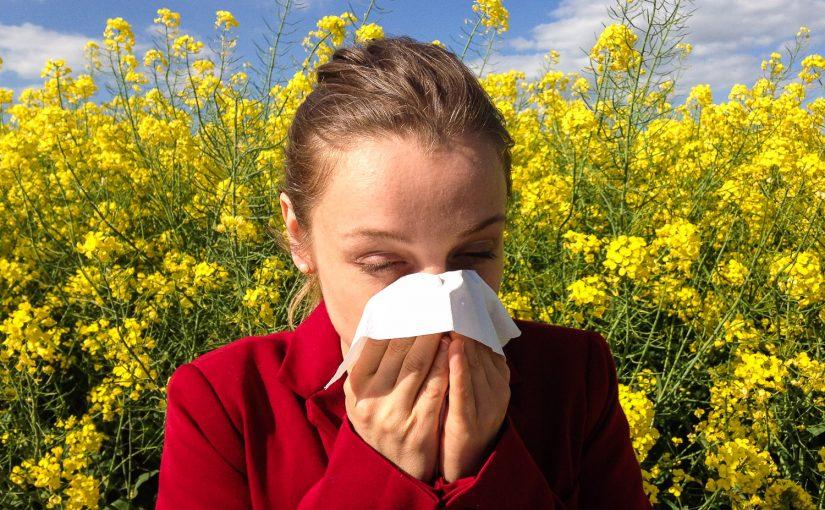 Аллергик с платком на фоне цветущих растений